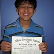 Photo of Brandon holding up his 6th Year National Piano Guild certificate